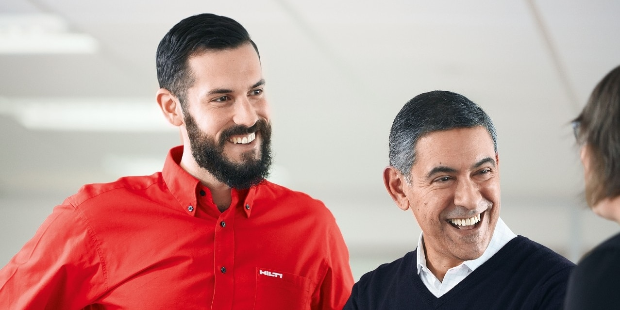 a hilti account manager and a customer smile at each other in a conversation